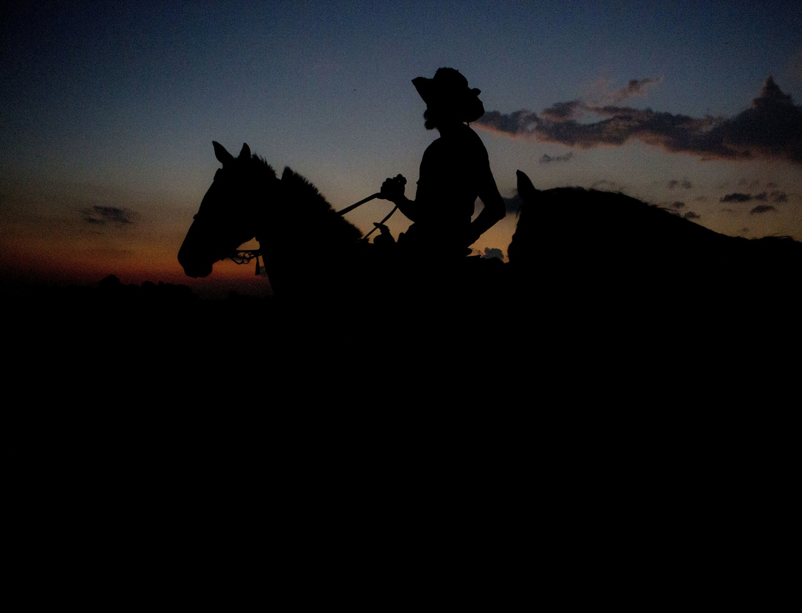 """Reggie Gough rides his horse Suzy while his other horse Mustang stays close with a halter carrying the horses to their resting stop. """"I'm not a cowboy, I'm a horseman, cowboy's chase cows, I give the cowboys a horse with tender hooves and a sore back, plus black man are afraid of ropes."""" Reggie Gough said while drinking a beer and saddling up his horses at the triple cross ranch. September 19th, 2017."""