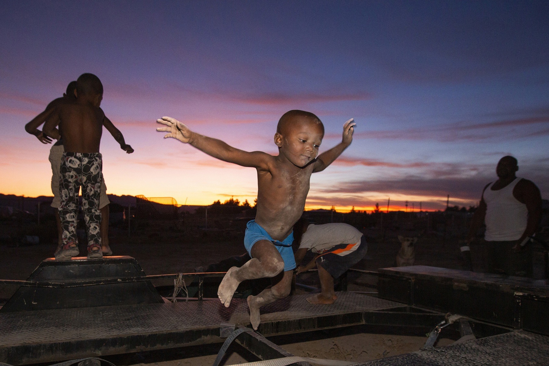 Da'Sean 'Tater Tot' Johnson, 2, jumps across a trailer while his father, right, warns him to watch himself and his brothers, left, watch the sun go down in the rural Nevada mountains on Wednesday, Aug. 21, 2019, in Pahrump.