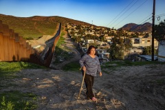 """A resident of Otay, a neighborhood in Tijuana, Mexico, says she sees a lot of journalists visiting her neighborhood to report on the new border wall being built. On March 13, 2018, President Trump visited a series of prototype walls, on the other side of the border from her home, as part his expansion of the wall along the southern border. Another resident of Otay, a self-described """"coyote,"""" says that helping people to cross illegally has become more difficult since the building of the new border fence. Jan. 25, 2019."""
