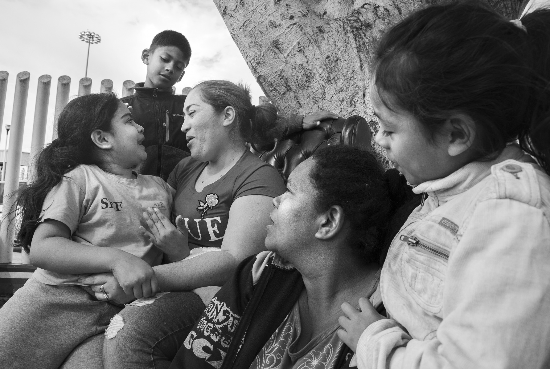 """""""We have been waiting for around three weeks,"""" says Ana Madrid Gomez (center), who laughs with her daughter, Sasha Madrid (far left) as they pass the time at the port of entry in Tijuana. All members of her group, including Taina Leiva, and her daughter, Ruth Leiva (far right) are migrants originally from Honduras."""