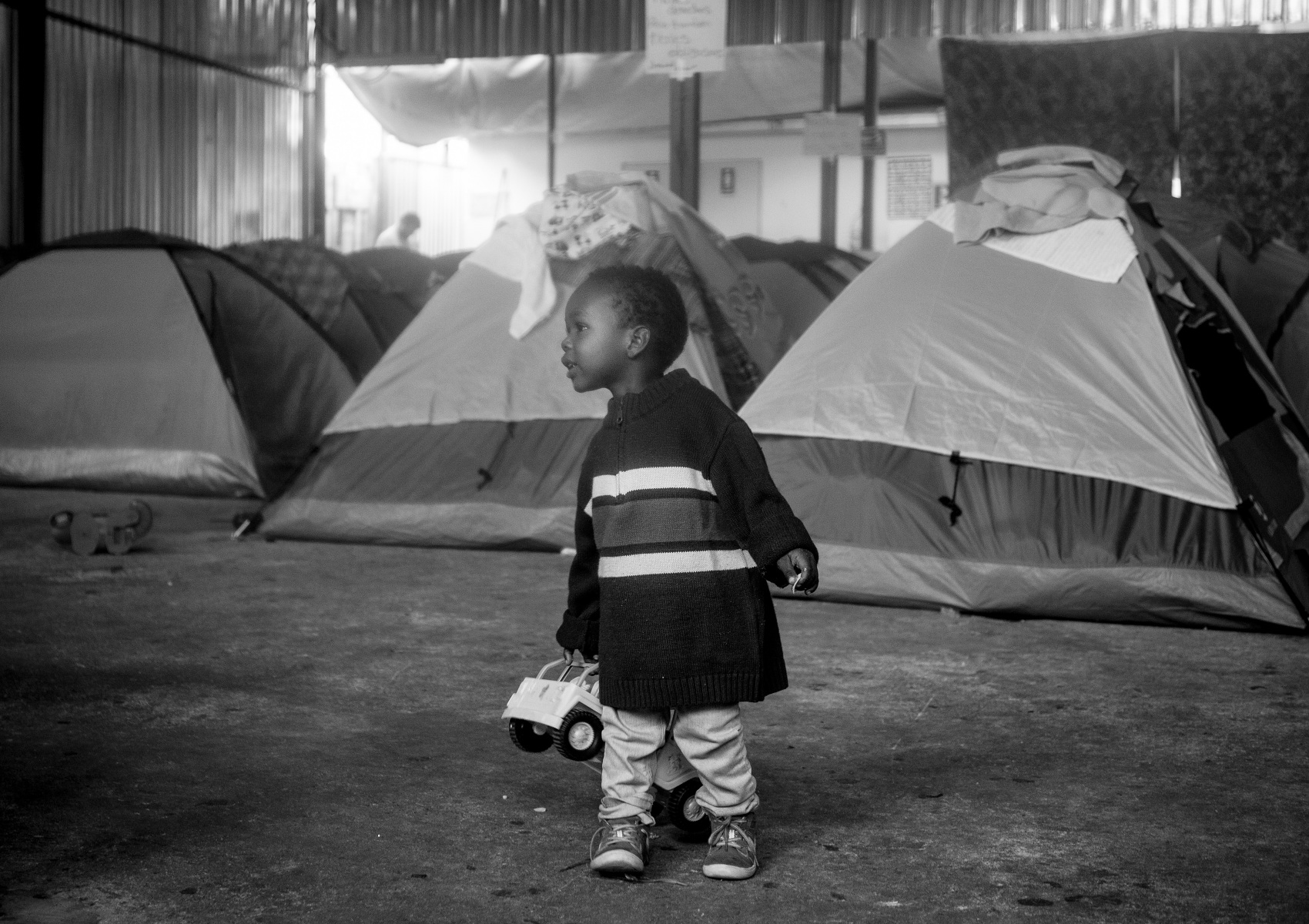 A population of Haitians, including this child playing with his toy truck, have traveled to Tijuana hoping for their number to be called to obtain asylum in the United States. They are waiting at the Benito Juarez shelter in Tijuana.