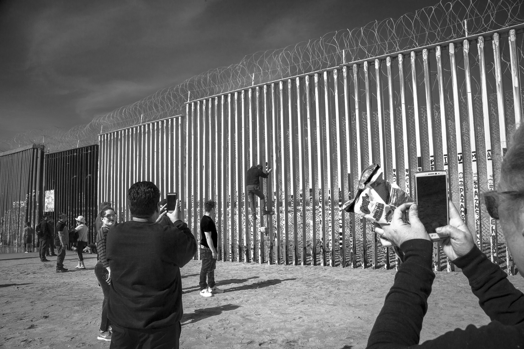 """Jose Neva, center, uses his phone to capture a man attempting to climb the border fence.  """"I just got here a week ago, but I'm trying to make it work. I want to go back to the other side the legal way, so I'm filing paperwork,"""" said Neva, who has two children living in Riverside, California."""