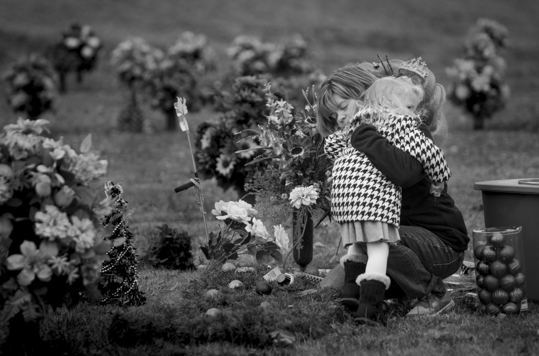 Melanie Hack, embraces her younger daughter Zoey, 3, near Reagan's grave at Monroe County Memorial Lawn in Tompkinsville, Kentucky. While other mothers' buy Christmas gifts for their children, Melanie buys ornaments and flowers to decorate her daughter's grave.