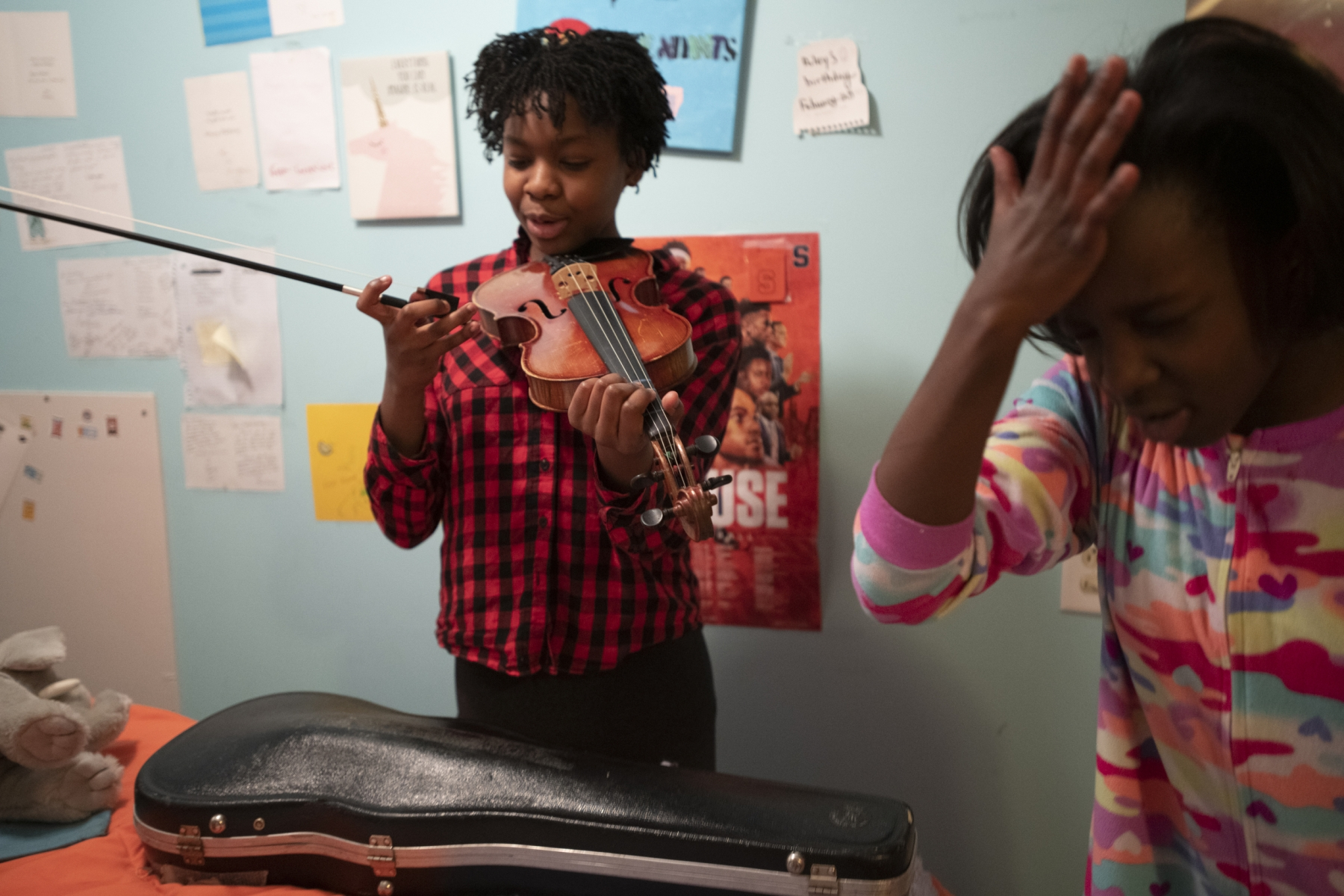 Amiah plays with Aubrey's violin in their house on Nov. 2, 2019. Both Aubrey and Amiah played violin in school but now only Aubrey plays.
