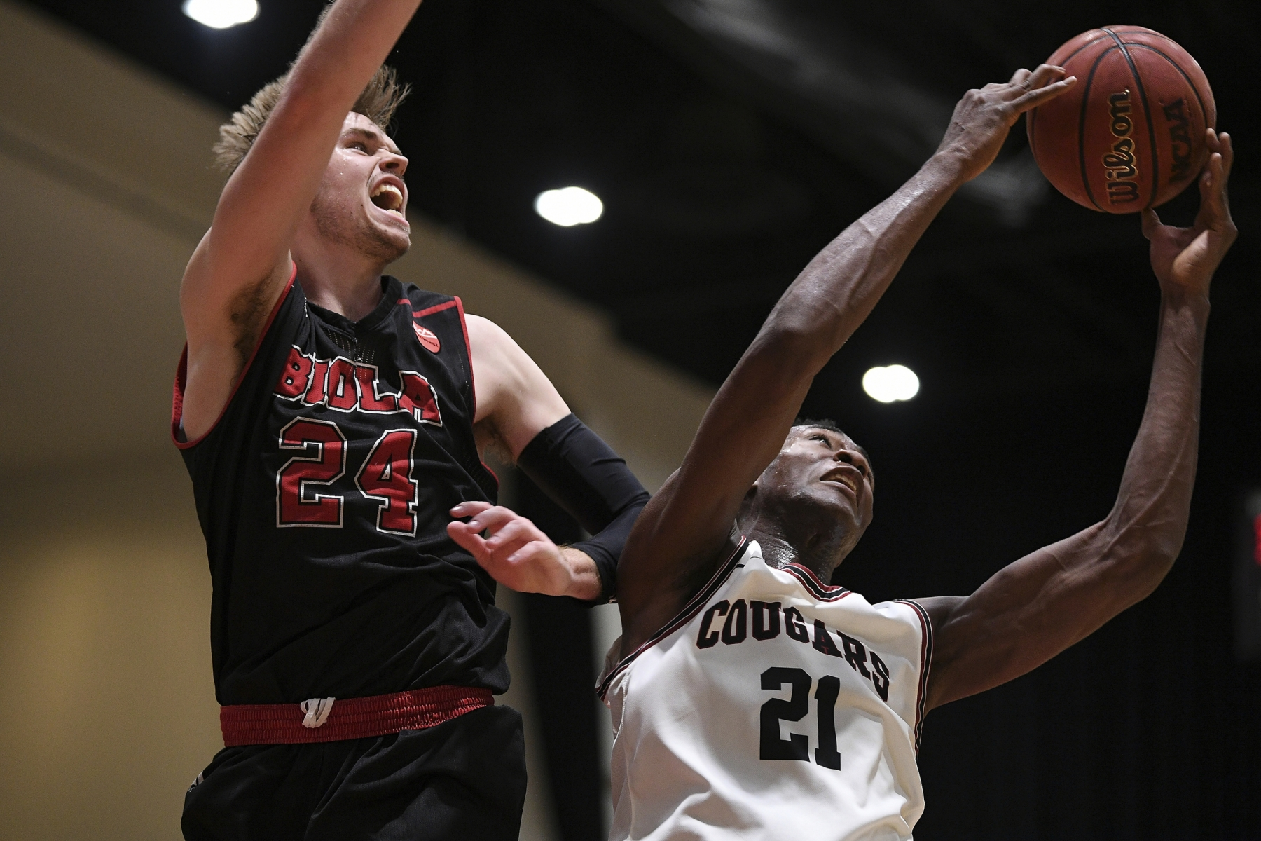 Azusa Pacific forward Selom Mawugbe (21) goes up for a layup against Biola forward Jesse Elrod (24) during a semifinal of the PacWest Men's Basketball Championship in the Felix Event Center at Azusa Pacific University Friday, Mar. 6, 2020, in Azusa.