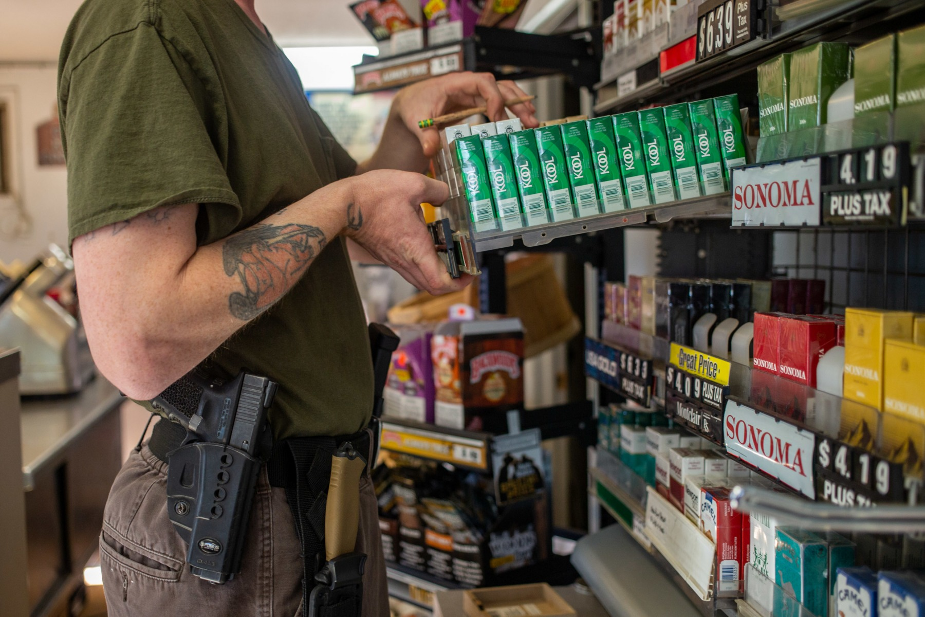Charles Bobo wears a Glock, three magazines and a knife on a tactical belt while he works the register at the gas station in the village. With no local law enforcement, residents feel a responsibility to protect their property, family, and the rest of the community.