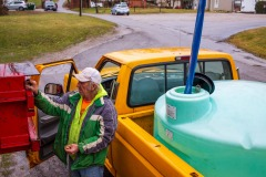 "John Singree hauls water in a 400-gallon tank he fills once a week to have water for plumbing, washing dishes, and doing laundry at home. There is a filling station in the center of town where residents who are not connected to the village water system can fill their bottles or tanks. ""It doesn't bother me, I'm used to it,"" John says."