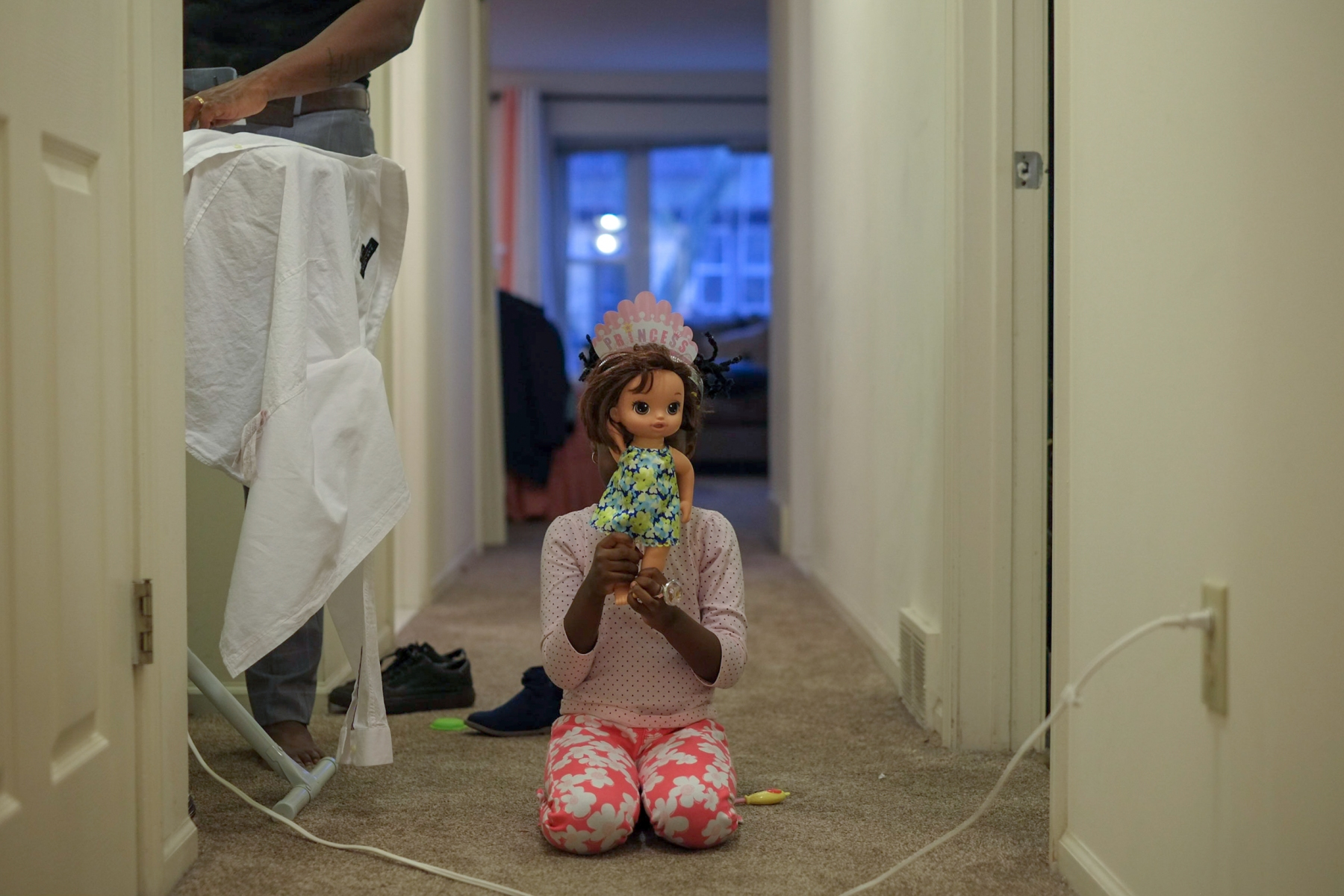 Kenza, 5, one of Mamba Hamissi and Nadia Nijimbere's twin daughters, plays with a doll in their apartment in Grosse Pointe Park, Mich. Nadia fled Burundi in 2013 when she was violently targeted for her work with a human rights organization. Nadia chose to go to Detroit, a city she heard about because of a shelter called Freedom House which provided pro-bono housing, social, and legal services to asylum-seekers. By the time Mamba's visa was finally accepted in 2015, he had missed Nadia's pregnancy, the twins' birth, and the first two years of their lives.