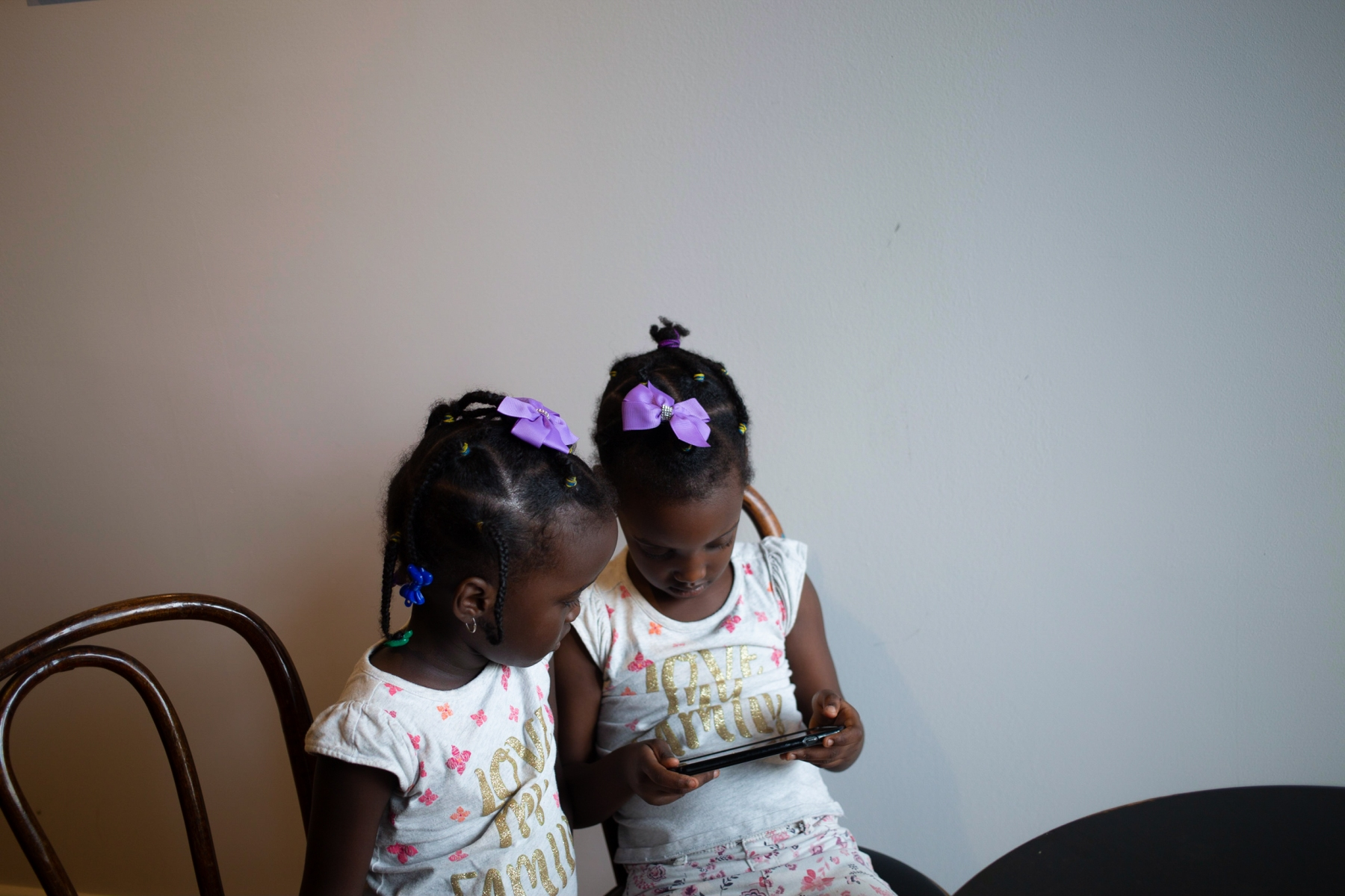 Mamba and Nadia's twin daughters, Kenza and Dieze, play games on Mamba's phone while he sells his Burundian-grown and Detroit-roasted coffee beans to a local coffee shop owner in Hamtramck, Mich.