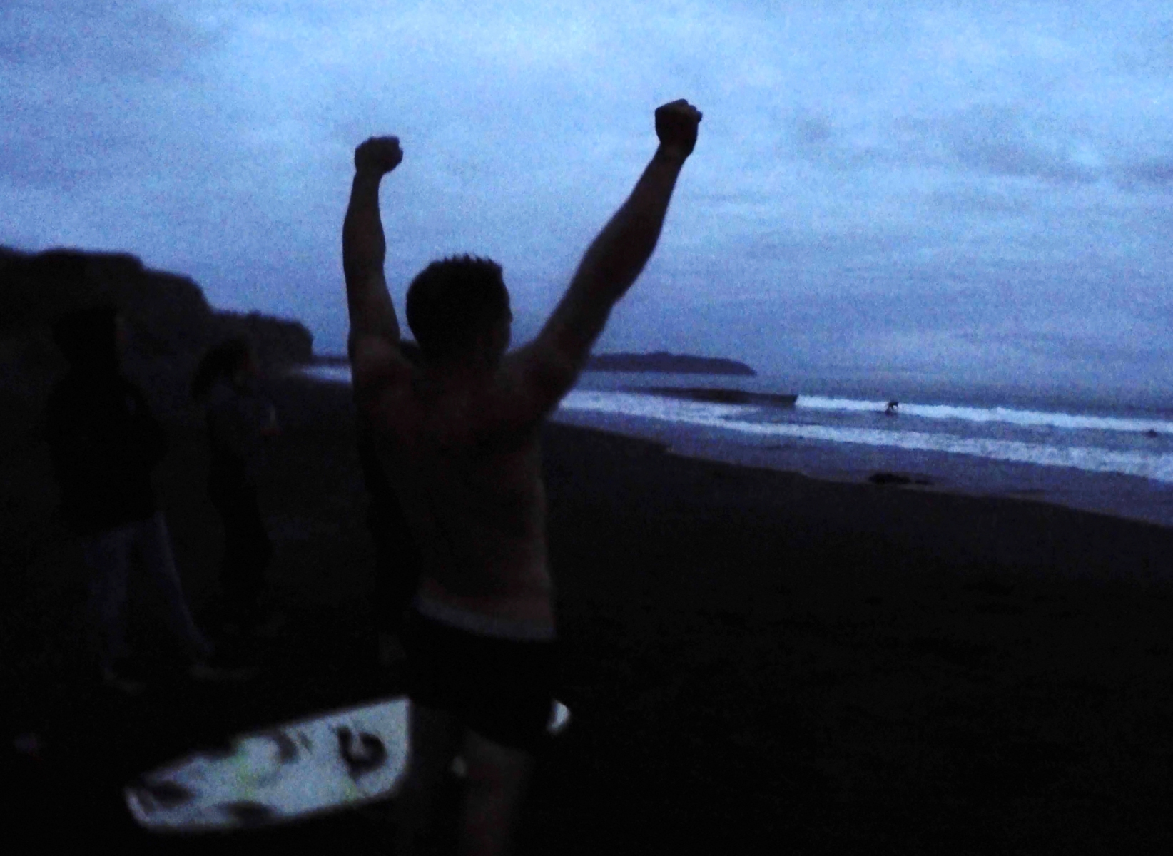 Andreas Carros cheers as Brayden Stevens surfs naked during a night surf session at a party, Saturday, August 1, 2020 at three mile beach