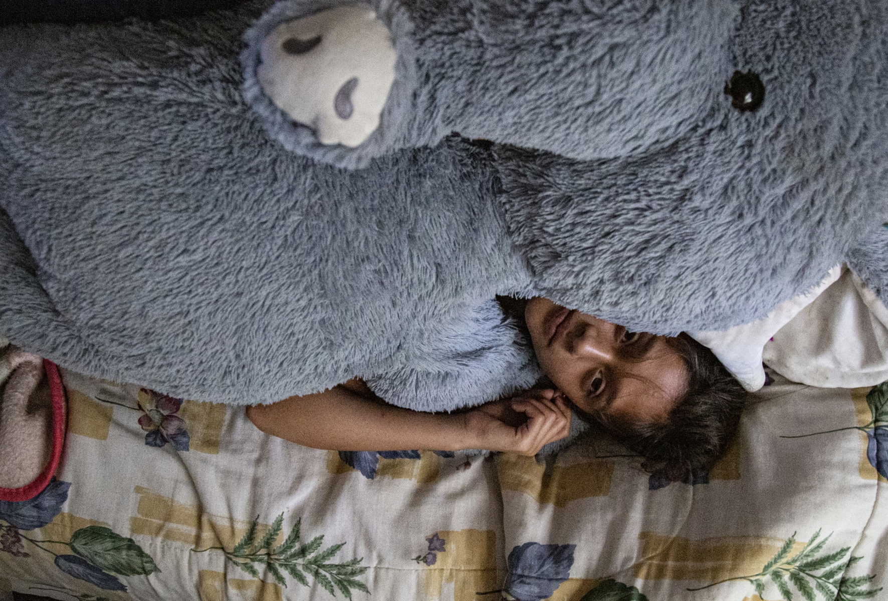 Camila lays on her bed with a giant stuffed animal, Sunday, Dec. 15, 2019 in Bradenton, Fla. Peace moves throughout the house but it is never silent. Sirens blare outside the window, people knock on the door and there is constant patter of feet across the tile floor. Sleep came during a few hours of stillness.