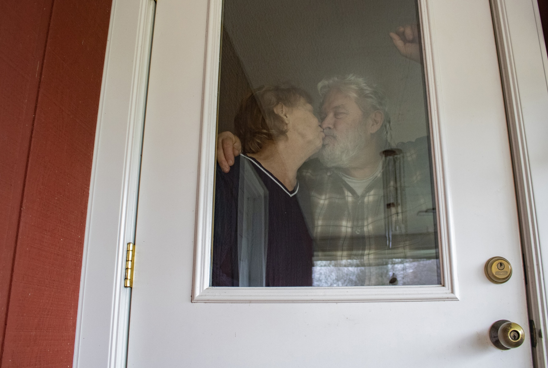 Carol and Jeff Knight share a kiss, Thursday, March 26, 2020 at their home in Mahomet, Ill. Both are in their late 70s. Carol expressed that they were lucky they had one another still. Their four daughters and four son-in-laws left food and supplies on their front porch and called them on the phone for the following three months as COVID-19 spread throughout the United States.