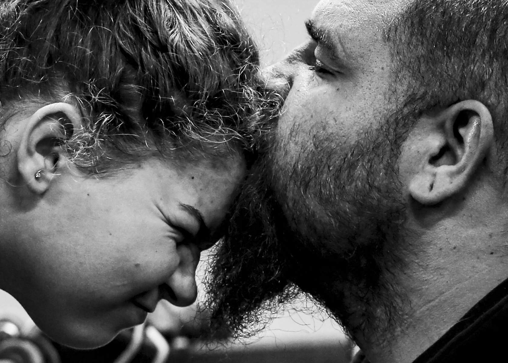 Nate kisses his daughter, Natalie, in the garage, Saturday, Jan. 18, 2019 in Muncie, Ind. Both Natalie and her mother, Ashley spent Saturday in the garage with the boys. Demolition Derbies are a whole family affair. Rebecca Slezak/JOUR437