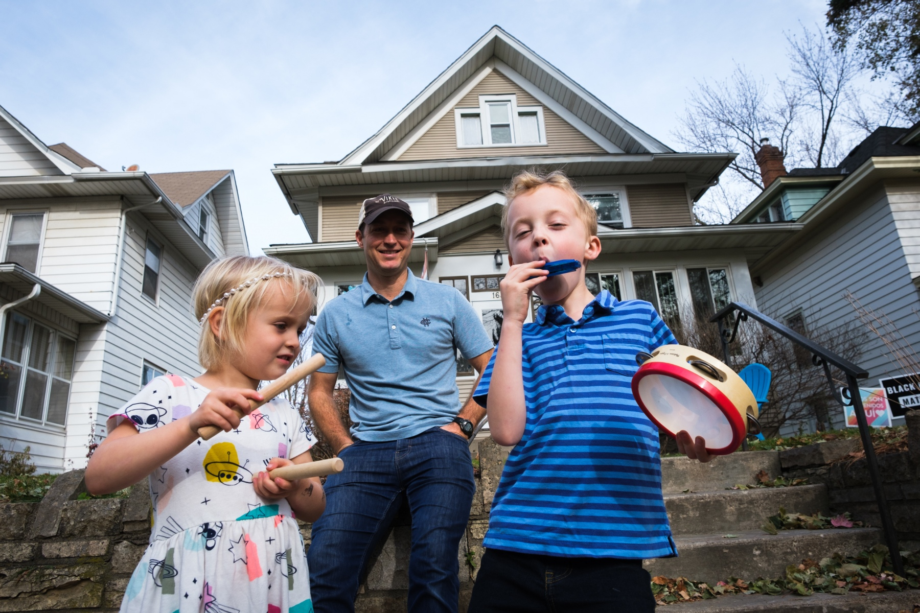 Endre and Silje Nelson play instruments on the sidewalk outside their house in Saint Paul after hearing that Joe Biden was declared the winner of the 2020 presidential election, while their father, Haakon Nelson, watches in the background on November 7, 2020.