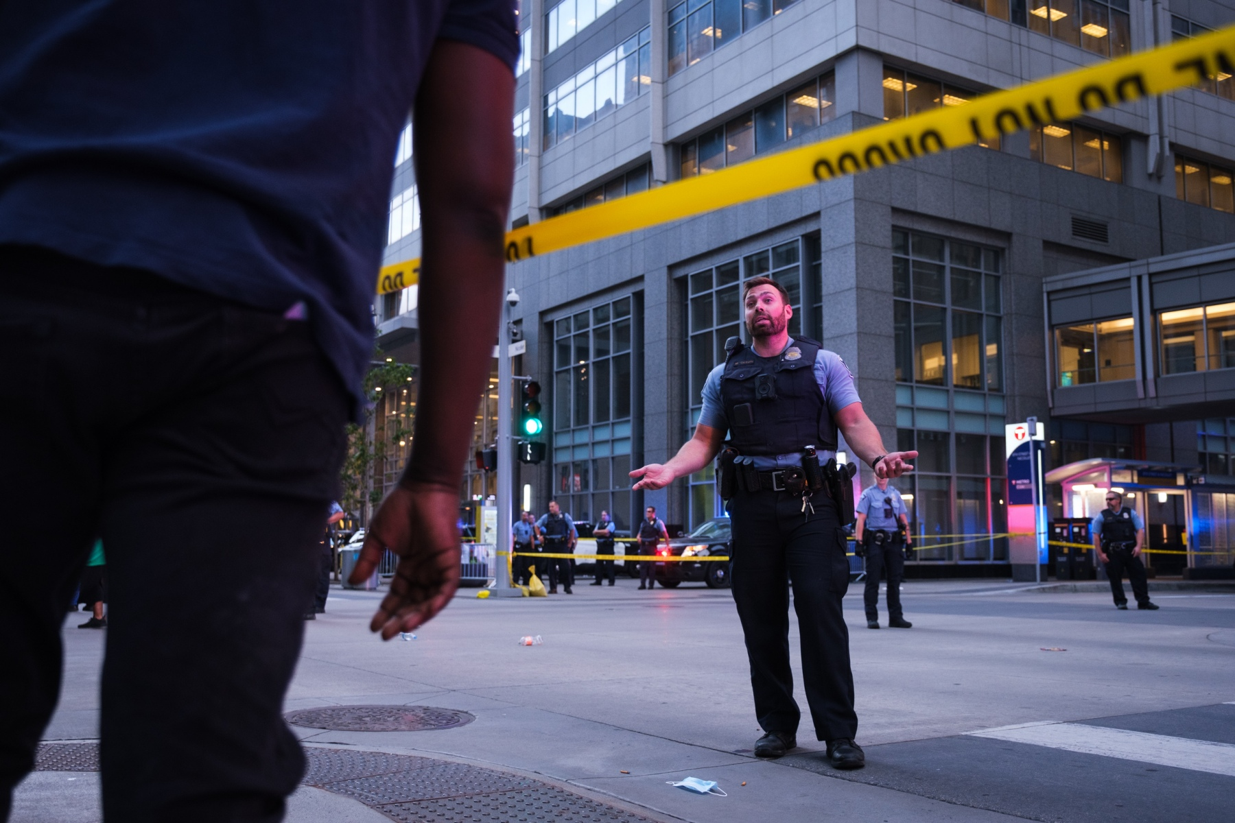 A Minneapolis police officer speaks to a bystander as police cordon off the area of Nicollet Mall near the shooting on August 26, 2020.