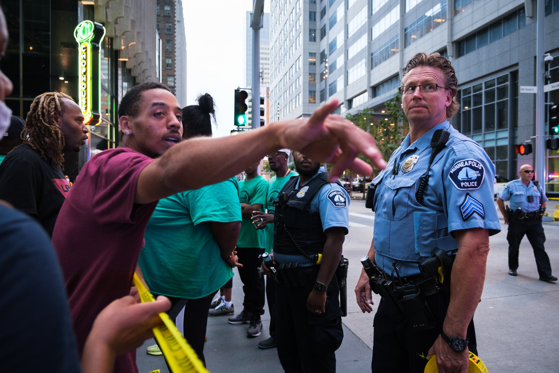 A bystander gestures to the section of the block where the shot went off on August 26, 2020.