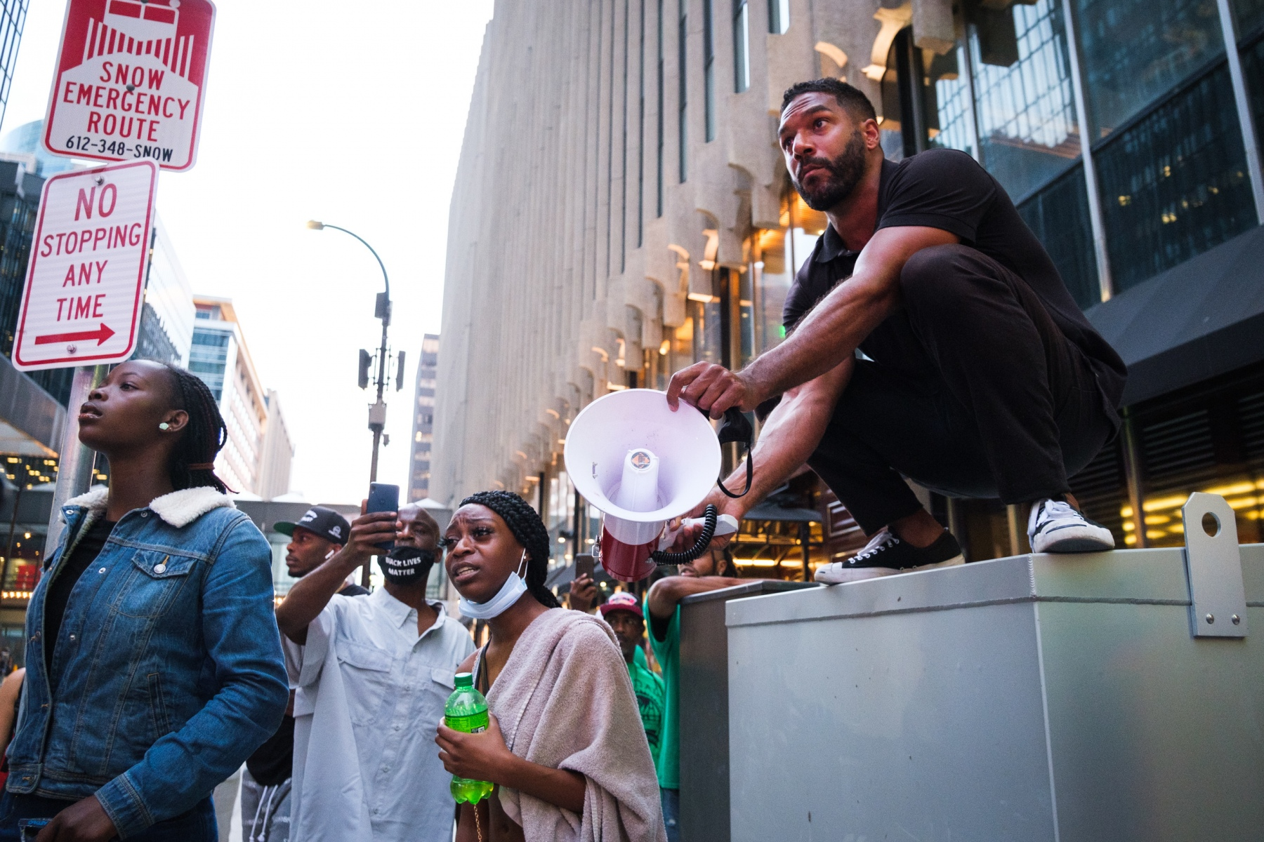 Black Lives Matter organizer Toussaint Morrison holds a megaphone for eyewitnesses to share their accounts of the shooting as tensions rise between bystanders and police on August 26, 2020.