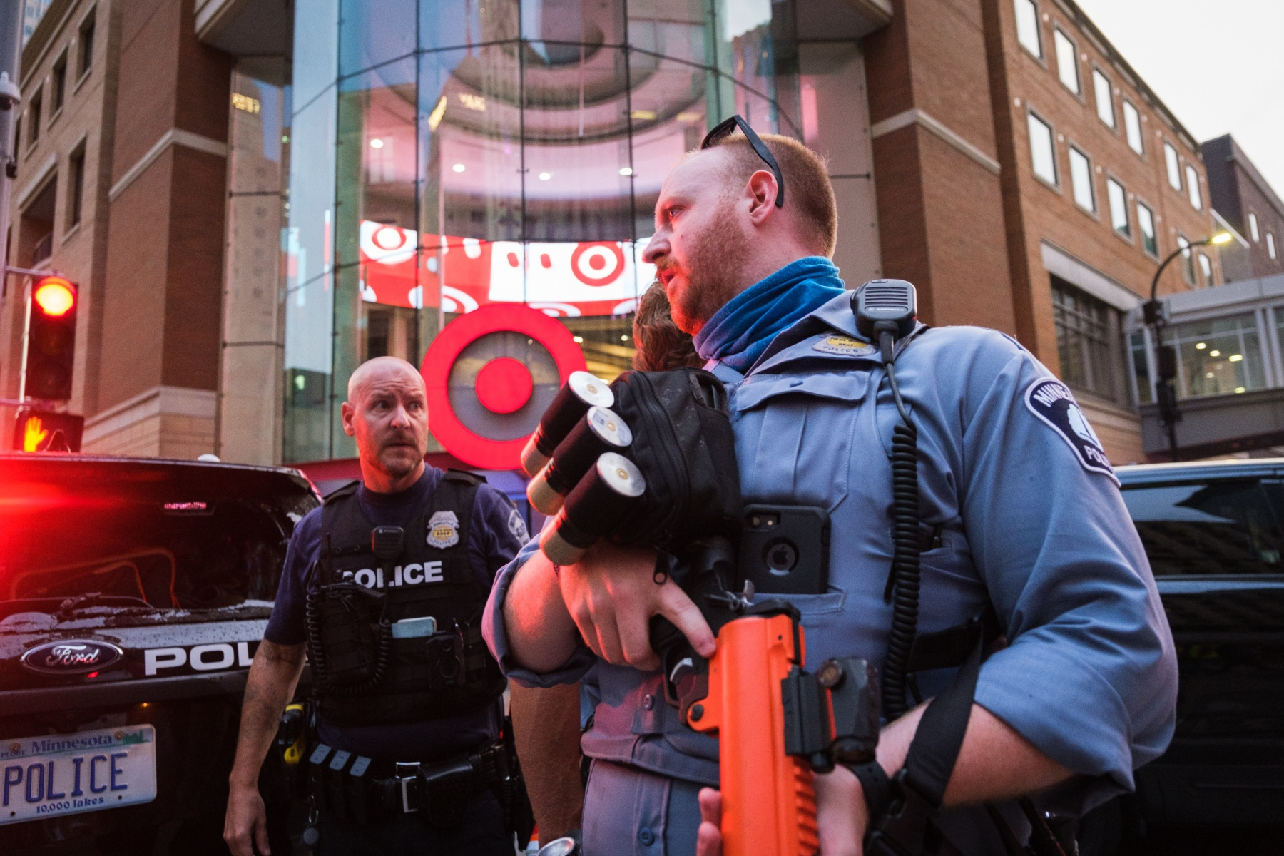 A Minneapolis police officer holding a projectile-launcher speaks to a fellow officer as bystanders continue to gather on August 26, 2020.