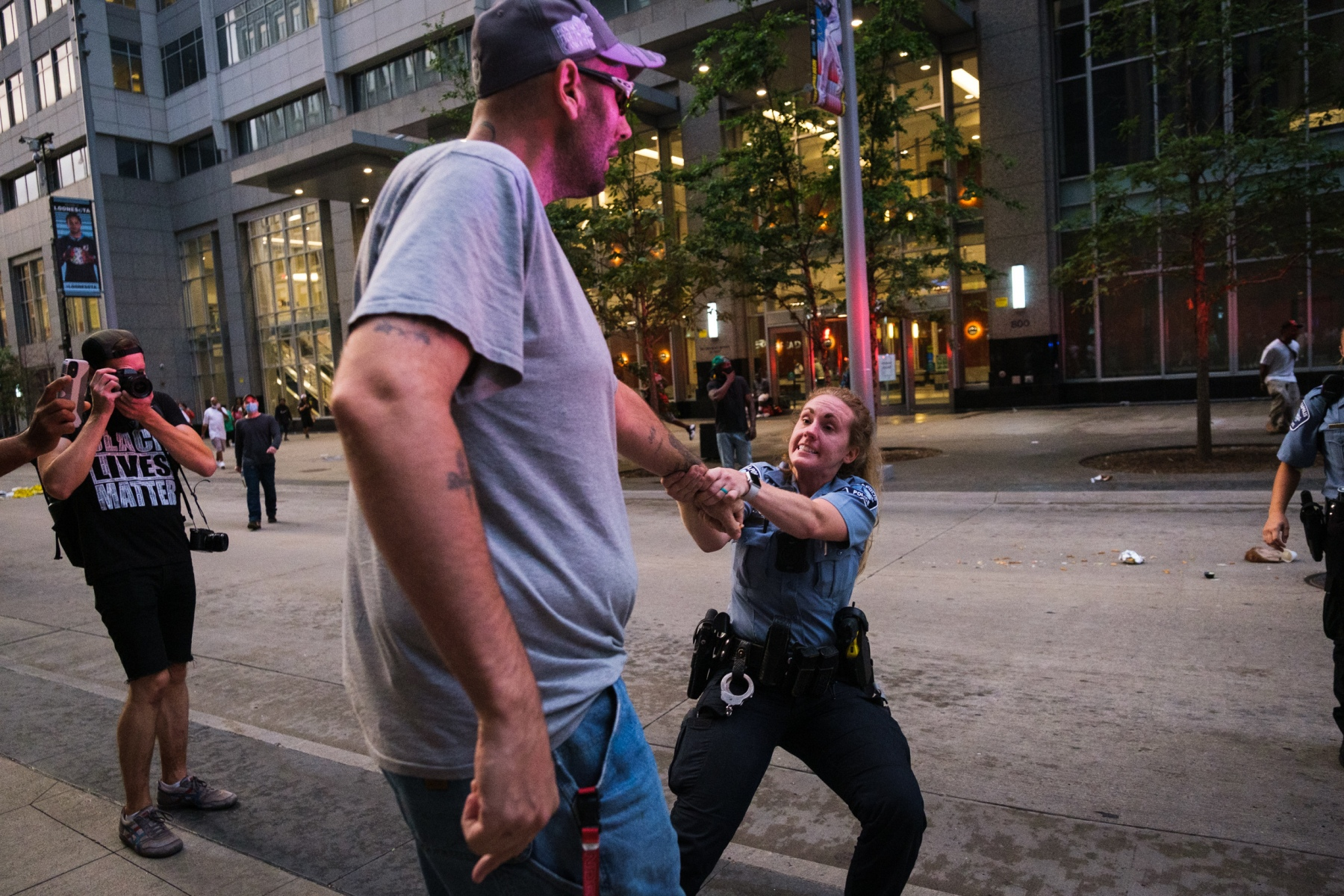 As protestors throw trash cans and other debris into the street in an attempt to block squad cars from leaving the area, a Minneapolis police officer attempts to arrest a bystander on August 26, 2020.