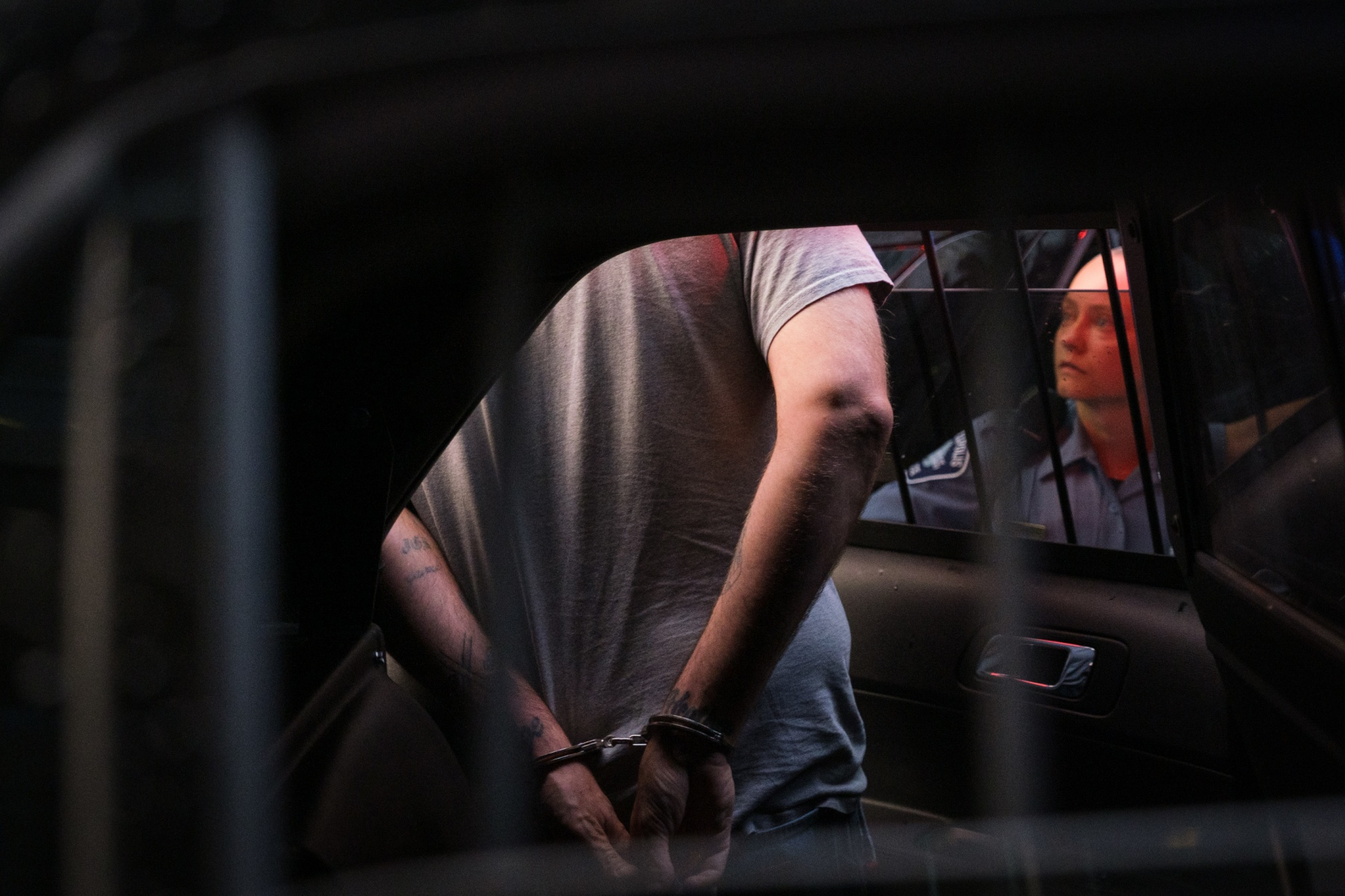 Minneapolis police officers arrest a bystander and place him in the squad car on August 26, 2020.
