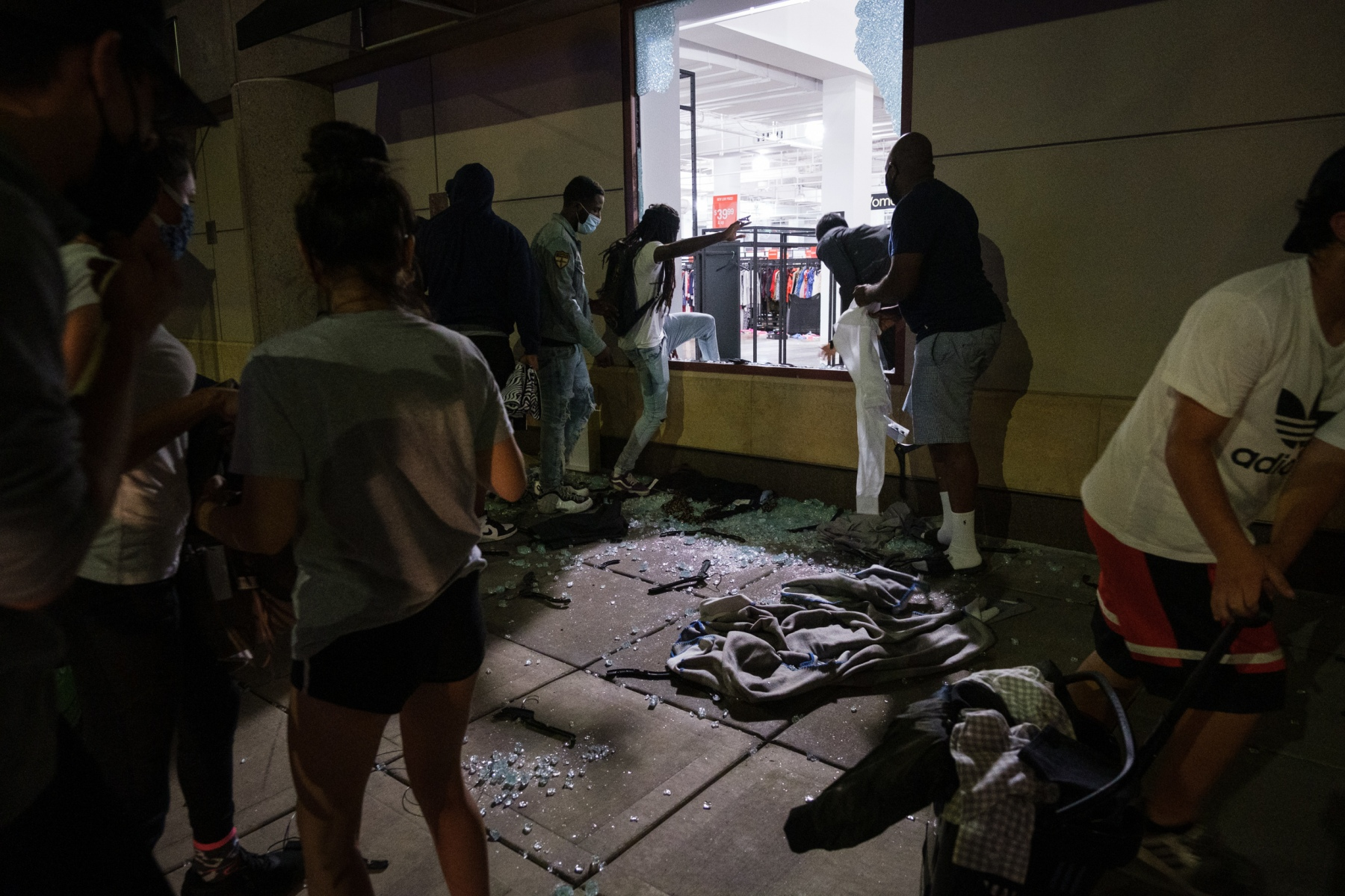 As night falls, looting continues to spread across the Nicollet Mall area of Minneapolis. People break into a clothing store along Nicollet Avenue on August 26, 2020.