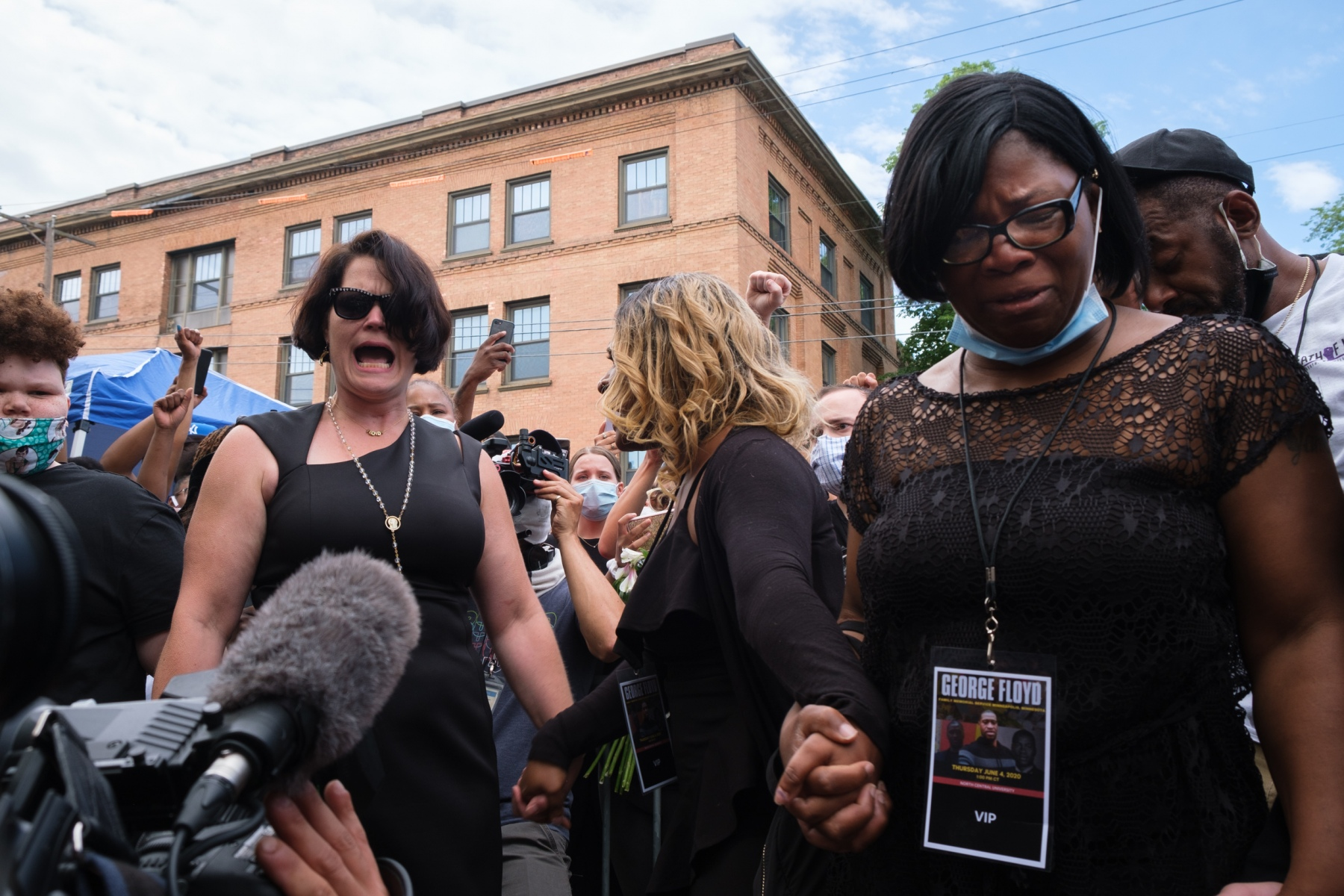 """Courtney Ross (left), Toshira Garraway (center), and Danielle Burns (right) link hands outside North Central University in Minneapolis on June 4, 2020, after leaving the funeral service for George Floyd. Burns' brother, Jamar Clark, was shot by Minneapolis police officers in 2015; Garraway's fiancee, Justin Teigen, died after an encounter with the Saint Paul Police in 2009; and Ross was Floyd's fiancee. """"They tried to separate us and keep us quiet,"""" screams Garraway. """"But we're together now. And we fighting together."""""""