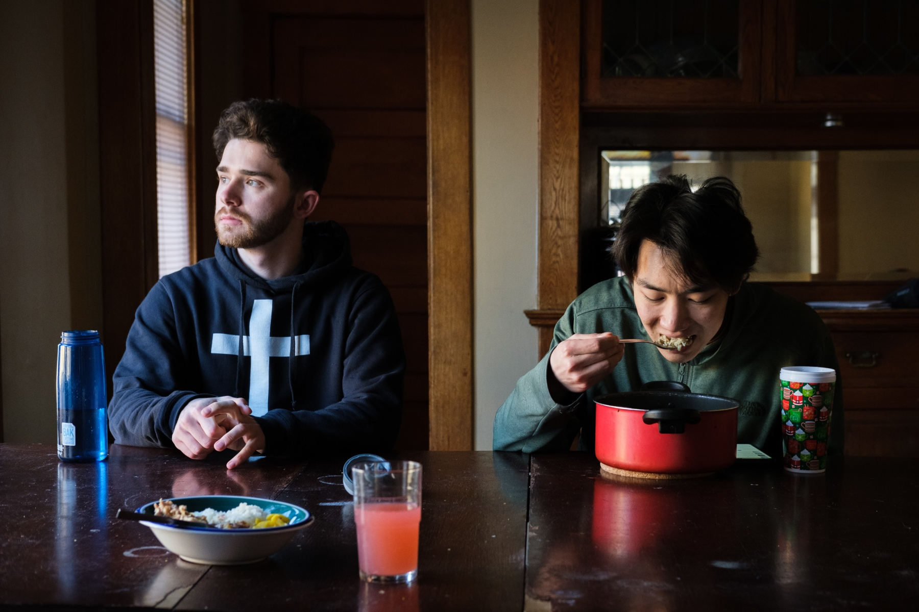Macalester College student Ben Harney (left) contemplates returning home to Vermont amid rising coronavirus cases in Minnesota as he and housemate, Tenzin Dothar (right), eat at the house dining room table on March 14, 2020.