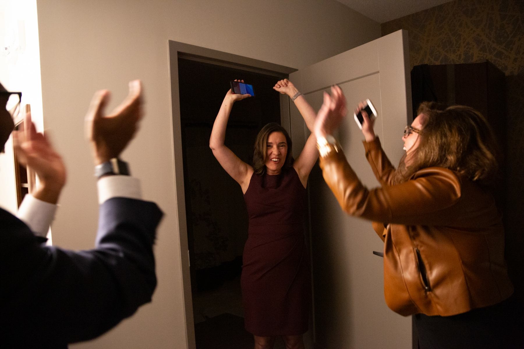 """On election night, after Justice Barbara Jackson, Anita Earls' leading opponent called her and conceded, Earls, Caroline Spencer, and José Morales scream in celebration in their hotel """"war room"""" in Raleigh, N.C.""""This is a moment I will never forget,"""" says Caroline Spencer, Earls' campaign manager.  Anita Earls became the 100th justice of the N.C. Supreme Court."""