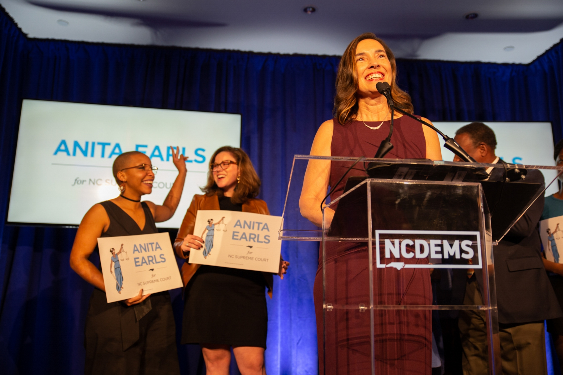 """Anita Earls takes the stage to accept the role of being the 100th justice of the N.C. Supreme Court at the North Carolina Democratic Party headquarters as her supporters cheer below. Juju Holton and Caroline Spencer, who both worked on the campaign, shed tears and celebrate behind her.""""We have a president who believes that he can by executive order erase the 14th amendment to the U.S. constitution,"""" Earls says in her speech. """"We have misguided partisans in our state who believe they should impeach justices that don't rule in their favor. I promise to resist partisan attacks on the judicial branch, which must remain independent and impartial in order for our democracy to succeed and thrive. Thank you for believing in the possibility that a civil rights attorney can run a state-wide campaign and win the trust of voters. Thank you for believing that you can make a difference because you have. And now, let's move forward without fear or favor."""""""